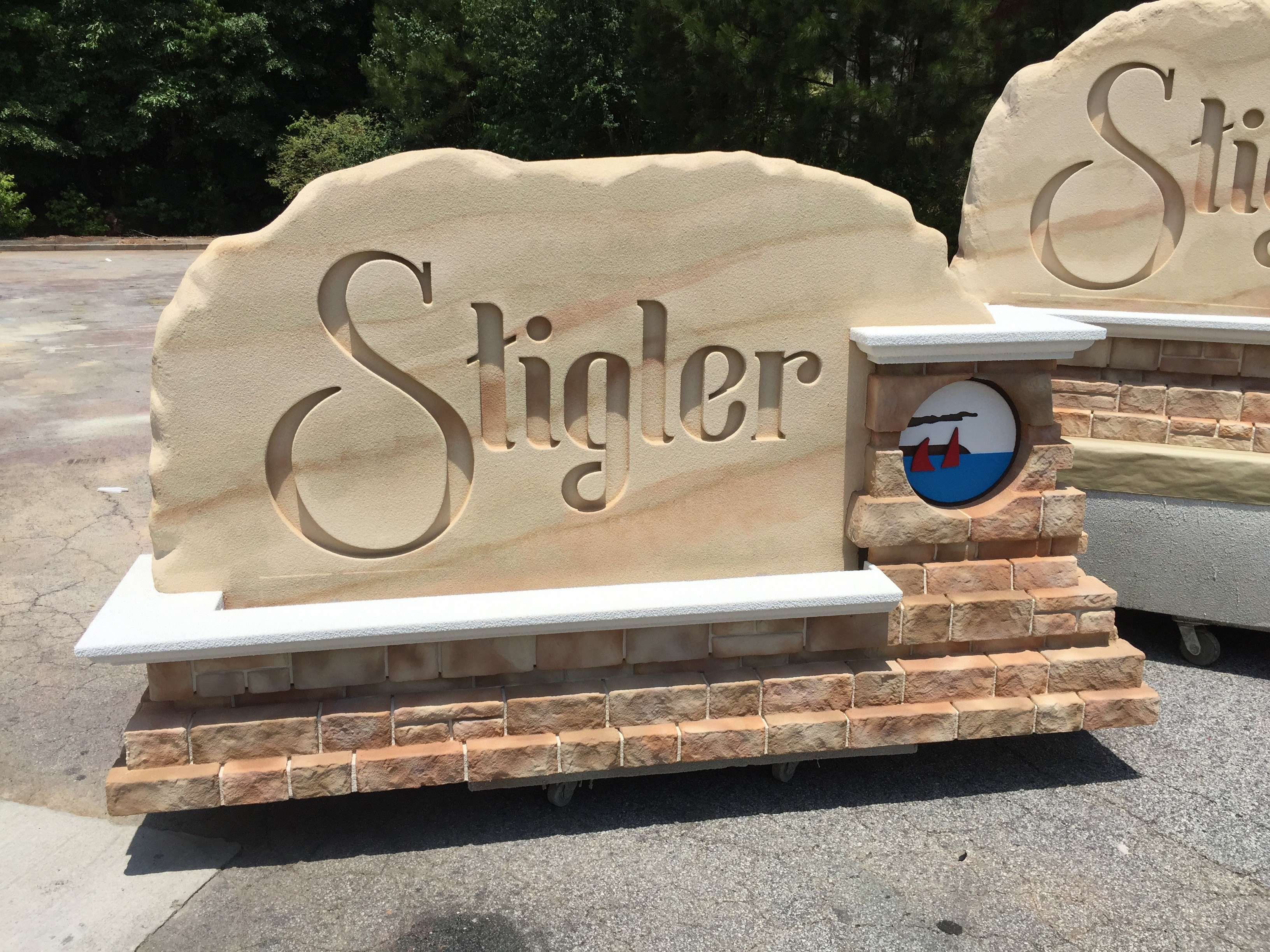 Faux sandstone city entrance sign monument with integrated lighting and embossed graphics in faux masonry.